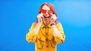 Happy smiling caucasian woman with two red hearts in hands, covering eyes, blue background. Love concept. Front view - Starpik Stock