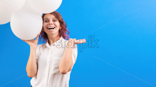 Happy smiling caucasian woman with white balloons, blue background. Holiday concept. Front view - Starpik Stock
