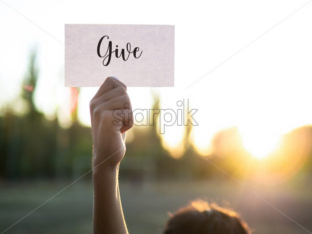 Male hand holding a note with word Give on it, setting sun - Starpik Stock
