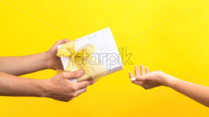 Man giving a gift box with red tape to a woman on yellow background. Hands. Love concept. - Starpik Stock