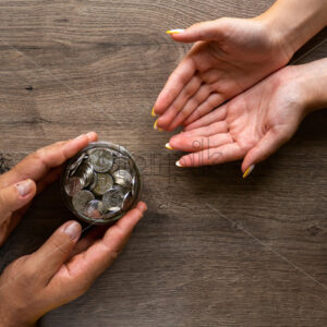 Man giving a woman the can with metal coins, people hands. Wooden background. Top view - Starpik Stock