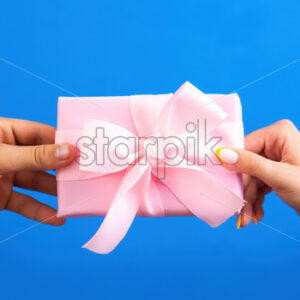 Man giving pink gift box to a woman on blue background. Two hands. Love concept. - Starpik Stock