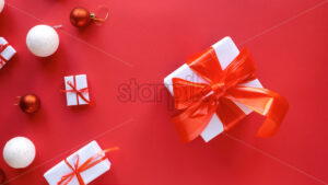 Multiple white gift boxes with red tapes and Christmas decoration on red background. Top view - Starpik Stock