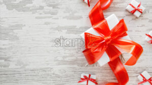 Multiple white gift boxes with red tapes on wooden background. Top view - Starpik Stock