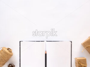 Notebook, gift boxes, twine. White background. Holiday concept. Top view - Starpik Stock