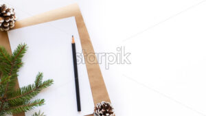 Notebook with a pencil, fir cones, Christmas tree branch. White background. Holiday concept. Top view - Starpik Stock