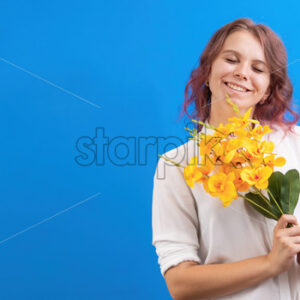 Pleased smiling caucasian woman with flowers and closed eyes, blue background. Holiday concept. Front view - Starpik Stock