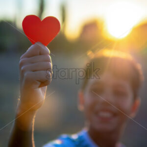 Smiling boy holding a red heart, setting sun. Love concept - Starpik Stock
