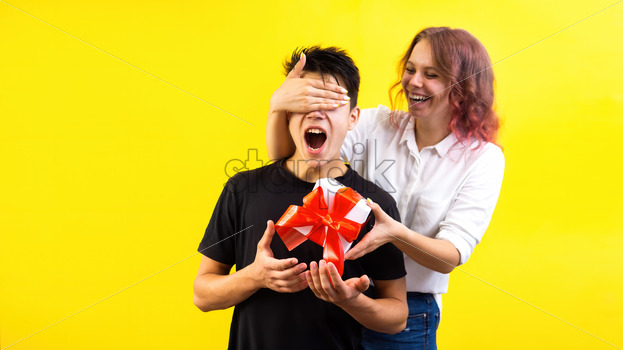 Smiling woman surprising a boy with a gift box with red tape closing his eyes, yellow background. Holiday concept - Starpik Stock