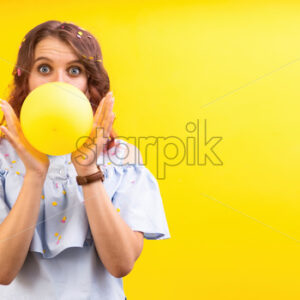 Surprised caucasian woman with a balloon between two hands, covering face, yellow background. Holiday concept. Front view - Starpik Stock