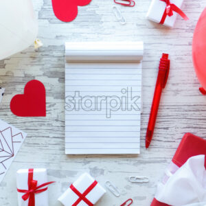 Table with gift boxes, note book, stationery, red hearts, balloons. Love letter concept. Top view - Starpik Stock