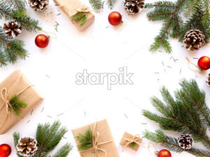 Table with holiday attributes, Christmas tree branches, decorations, gift boxes. White background. Holiday concept. Top view - Starpik Stock