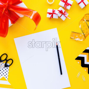 Table with things for preparing gifts, gift boxes, tapes, stationery. Yellow background. Holiday concept. Top view - Starpik Stock