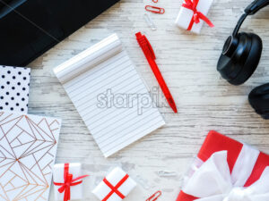 Table with things for work, gift boxes, note book, headphones, laptop, stationery. Work concept. Top view - Starpik Stock