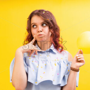 Thinking caucasian woman with a balloon in one hand, yellow background. Holiday concept. Front view - Starpik Stock
