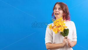 Thinking smiling caucasian woman with flowers and closed eyes, blue background. Holiday concept. Front view - Starpik Stock