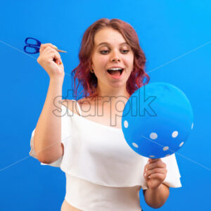 Thinking surprised caucasian woman with a balloon and scissors in hands, preparing to blow, blue background. Holiday concept. Front view - Starpik Stock