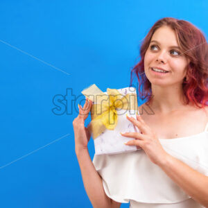 Thinking surprised caucasian woman with a gift box in hands, blue background. Holiday concept. Front view - Starpik Stock