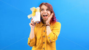 Thinking surprised caucasian woman with a gift box in hands near the head, blue background. Holiday concept. Front view - Starpik Stock