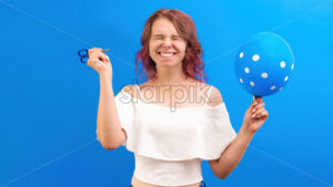 Thinking surprised caucasian woman with closed eyes, with a balloon and scissors in hands, preparing to blow, blue background. Holiday concept. Front view - Starpik Stock