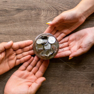Transfer of the can with metal coins from man to woman , people hands. Wooden background. Top view - Starpik Stock