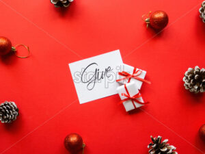 Two white gift boxes, note with message and Christmas decoration. Red background. Holiday concept - Starpik Stock
