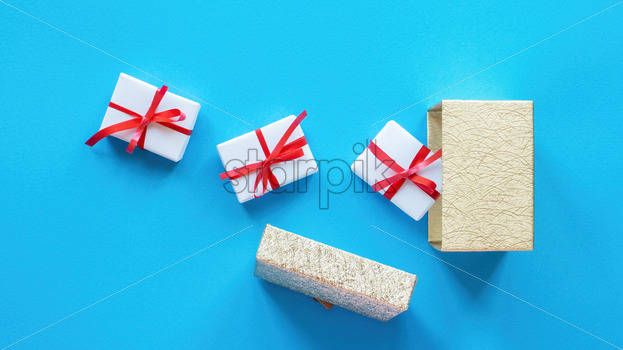 White gift boxes with red tapes and opened box on blue background. Top view - Starpik Stock