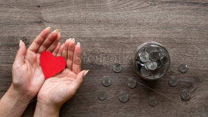 Woman is holding a red hearth, the can with metal coins inside and around it. Woman hands. Wooden background. Top view - Starpik Stock