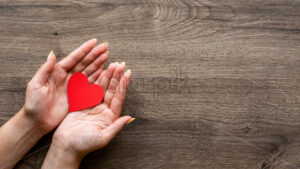 Woman is holding a red hearth. Woman hands. Wooden background. Top view - Starpik Stock