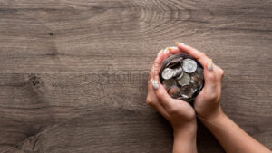 Woman is holding the can with metal coins. Woman hands. Wooden background. Top view - Starpik Stock