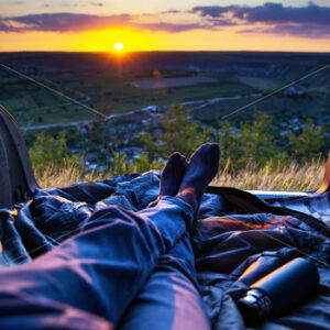 A man lying in the opened trunk of the car with view on the nature of Moldova, fields, hills at sunset - Starpik Stock