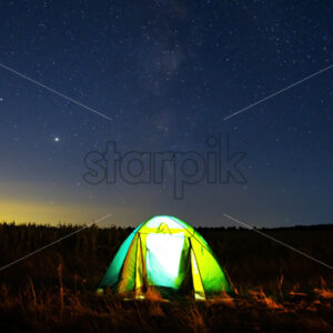 A tent in a field with light inside and sky full of shining stars in the background, Moldova - Starpik Stock