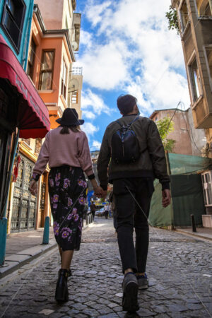 A walking couple holding each other walking on a pedestrian street, wide angle shot, rows of buildings in Istanbul, Turkey - Starpik Stock