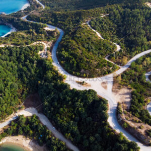 Aegean sea cost of Greece, twisting road, hills covered with lush greenery, view from the drone, Greece - Starpik Stock