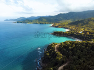 Aerial drone view of blue sea and windy mountain roads in Halkidiki, Greece - Starpik Stock