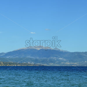 Blue background with mountains and sea in Greece - Starpik Stock
