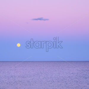 Dark purple sky with yellow moon over sea after sunset in Greece - Starpik Stock