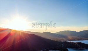 Drone panorama of big red sun in Halkidiki with blue sea and mountains, Greece - Starpik Stock
