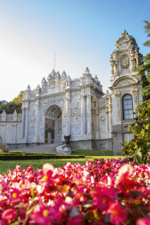 Facade of the Dolmabahce Palace with gardens full of greenery and flowers in front of it in Istanbul, Turkey - Starpik Stock