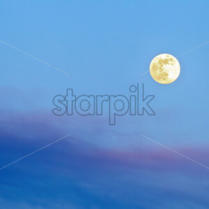 Huge yellow moon in the sky consisting of shades of blue and violet - Starpik Stock