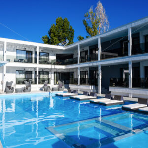 Inner court of Avaton Luxury Resort with a pool, sunbeds and multiple hotel room's entrances in Asprovalta, Greece - Starpik Stock