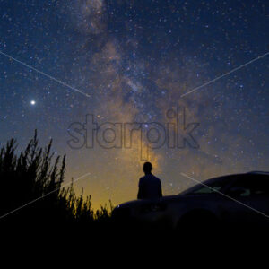 Man with his car looking at sky full of shining stars, long exposure, Moldova - Starpik Stock