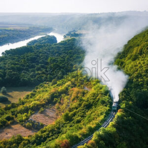 Moving train on railway with high column of smoke, flowing river, hills and railway on the foreground, fields on the other shore in Moldova - Starpik Stock