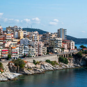 Multiple buildings located on the Aegean sea cost, road passing over the rocky coastline, green hill on the background in Kavala, Greece - Starpik Stock