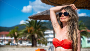Portrait of a caucasian woman in sunglasses and red swimsuit with raised hand under a umbrella on the beach in Riviera, Greece - Starpik Stock