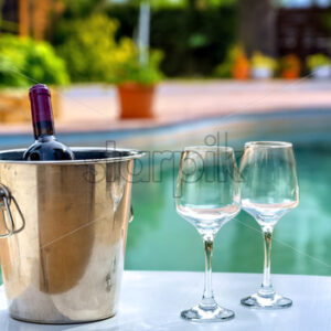 Red wine bottle and glasses by the hotel pool - Starpik Stock