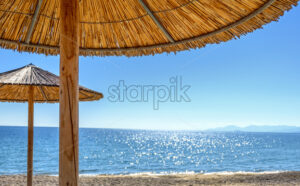 Reed umbrellas and sun beds at the empty beach in Asprovalta, Greece - Starpik Stock