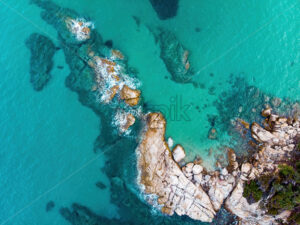 Rocky coastline of the Aegean sea with transparent blue water, view from the drone, Greece - Starpik Stock