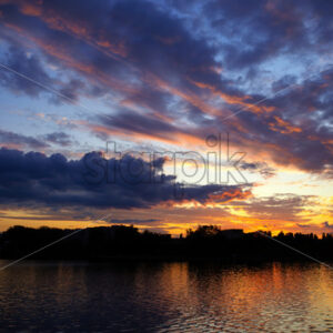 Sunset in Moldova, lush clouds with yellow light reflected in surface of the water on the foreground - Starpik Stock
