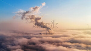 View of a thermal station in the distance above the clouds, columns of smoke, ecology idea - Starpik Stock